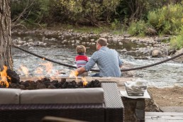 Father son looking at river with cozy couch and fire in foreground