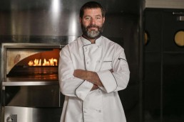 Chef standing in front of oven in open kitchen